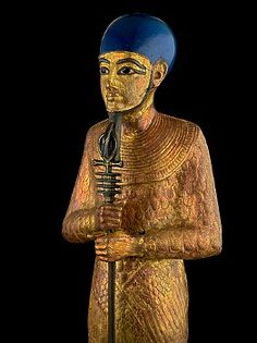 """""""Statue of Ptah from tomb of Tutankhamun In this figure Ptah is clearly identifiable by its mummy wrappings and tight-fitting skullcap, the base is shaped like a throne platform, a broad collar hangs around his neck and his costume has been engraved with feathers (rishi), the god holds a scepter along with an ankh for life and a djed pillar for stability. 