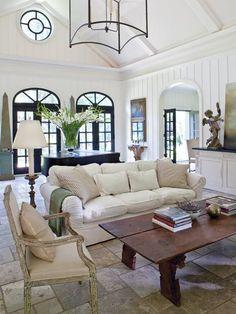 neutral sofa, stone floors and black doors...