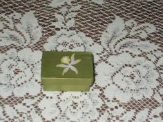 Earring sized little gift box in a metallic green with a floral flourish