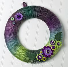 Kathleen George shares with us the prettiest Spring Yarn Wreath. The variegated yarn, in shades of lavender and lime, does the design work for you, layering on the stripes as you go. Crochet Wreath, Felt Wreath, Wreath Crafts, Diy Wreath, Yarn Crafts, Diy Crafts, Yarn Wreaths, Wreath Ideas, Door Wreaths