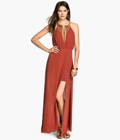 Long elegant dress with a metal decoration at top. Opening at back with buttons at the back of neck, seam at waist, and wrap-front skirt with high slit. Elegant dress for fancy events.