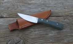 Small hunting/ EDC knife from 1084 high carbon steel, homemade denim micarta handle, & matching custom leather sheath. Check out my other works and see what's for sale. Message with any questions: http://www.facebook.com/JaredKramerStudios http://www.etsy.com/shop/JaredKramerStudios