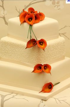 Pretty orange flowers. Square cake.  Maybe a little more design on the tiers? Or perhaps orange bands instead of white!