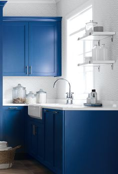 Subtle wall covering and those bold blue cabinets!!