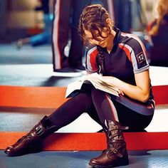 Jennifer Lawrence-reading harry potter during a break.  10,000 points to district 12