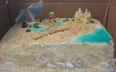 Beach Cake - crushed vanilla wafers for the sand...people, sand castle, shells, starfish, flipflops, lotion bottle, bag with towels, bucket and other decorations are fondant. The water is tinted gel icing...umbrella was paper, made on computer...supported w/plastic dowel.