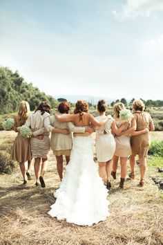 I like how all of the bridesmaids are wearing different dresses but yet all in the same color range.