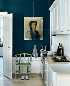 Warm navy blue wall with oil painting in bright white kitchen.