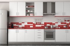 The random nature of the placement of the splashback tiles in this red and white kitchen is oddly appealing.
