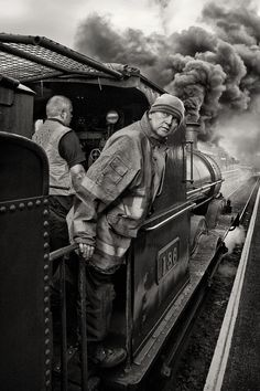 An outstanding and magnificent black and white image of a railroad operator poking his head outside, as plumes of smoke from the steam locomotive explode overhead. This image looks like a painting! Image by Gary McParland.