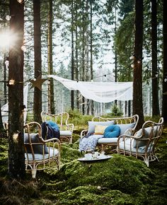 A rest area in a country wedding, with rattan armchairs, many cushions and garlands of lights.