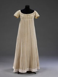 V & A Museum Item number T.268-1971. Dress c1812. Dress made of warp-knitted fabric, probably cotton. With a pattern of alternating stripes of close 'plain' knitting and open work. The sleeves and a band inserted around the neck are also in knitted cotton with a smaller pattern of alternating plain and open work. fastens at centre back. Lined with a dark gold silk, and the bodice and seams with a lighter yellow silk.