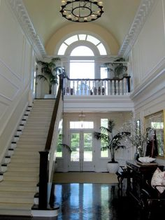 open foyer, arched window overlooking stairs, french doors leading to backyard from foyer