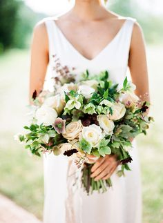A romantic bouquet with cream-colored roses combined with mauve and pale-green hellebores | Brides.com