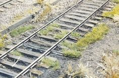 The grass clump near the inside of the rail doesn't interfere with operation at all.