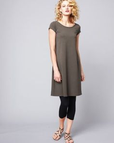 The basic black dress is updated by Eileen Fisher in soft organic cotton with a little Lycra to help it keep its easy A-line shape. From the graceful ballet neck and cap sleeves to the below-the-knee hem, this versatile style can be dressed up or down to go anywhere. USA.