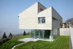 Top-heavy geometric concrete home in daylight