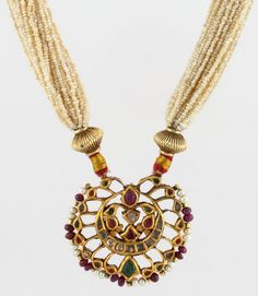 A REVERSIBLE PEARL AND GEMSET NECKLACE Designed as reversible openwork pendant, kundan-set with table-cut 'polki' diamonds, rubies, emeralds and pearls, strung on multiple rows of seed pearls, and joined by an adjustable silk cord, with a total gemstone weight of approximately 12.00 carats, a total diamond weight of approximately 2.00 carats, and a total pearl weight of approximately 52.00 grams, mounted in gold.