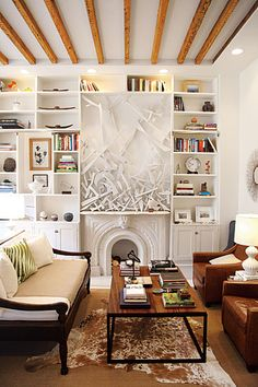 I love the exposed beams, built-in bookshelves, wood and metal table, and leather arm chairs.