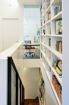 """This bookcase """"lives"""" over the staircase 90% of the time. However, when the homeowners need access, it slides into the living room and has a ladder for reaching everything."""