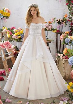 This Glamorous Off-the-Shoulder Bodice Accented in DiamantéŽ and Pearl Beading on Lace Comes Together Beautifully with a Simple, Layered Tulle Ballgown Skirt. Colors Available: White, Ivory, Ivory/Nud