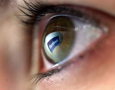 Close-up of eyeball with Facebook reflection