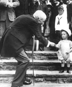 1914, John D. Rockefeller hands out dimes to poor children in a staged propaganda attempt to salvage his image.