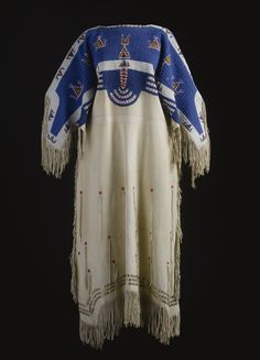SIOUX BEADED AND FRINGED HIDE DRESS    composed of tanned deer hide, the yoke sewn in numeorus colors against a bright blue glass beadwork ground, with typical geometric motifs, the body, with beaded pendants and rows of metallic spangles at the hemline.    width across the yoke 57 in.