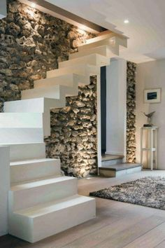 Love the clean white concrete stairs in front of the rough textured stone wall!