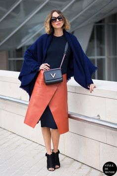 How to Layer a Skirt Over Pants or a Dress - orange leather envelope skirt layered over a midi dress + styled with a navy blue scarf, boxy cross body bag, and ankle boots