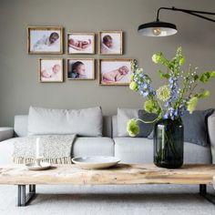 Zithoek met grijze bank en houten fotolijsten tegen de groene wand