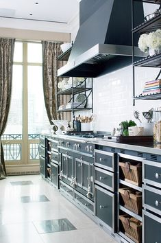 French La Cornue range with its matching black hood and cabinets trimmed in silver. That ceiling-high backsplash of classic white subway tiles and silver nickel countertops ....YUM !