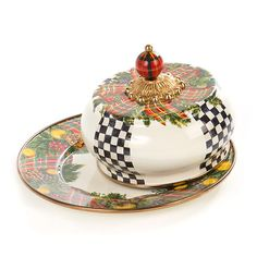 Evergreen Enamel Butterhouse  MacKenzie-Childs introduces new serving pieces to its stunning collectible enamelware, which is sure to become a perennial favorite during the season of nostalgia. Each piece is decaled with tartan plaid ribbons and golden apples, with greenery of blue spruce, red cedar, Scots pine, live oak, and holly.