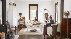 Despite dark hardwood floors and an antique brown leather-studded naval captain's chair, the living area feels light and bright, thanks to tall windows, linen sofas, and a 1900s beadboard jelly cupboard that hides the television. The coffee table, which sits atop two rugs—one jute, one hemp—is a repurposed, cut down baker's table. Lindsea liked the look of the chipped paint so much that she sealed the top as it was.