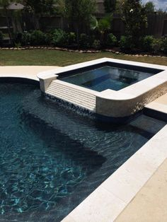 Geometric pool and spa with curves. Travertine coping and scabos on outer trim with two water bowls.