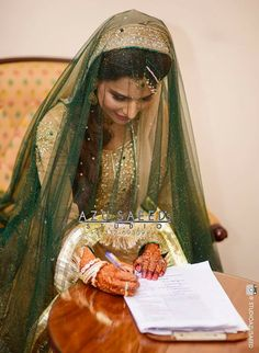 Pakistani bride having signing the marriage contract.