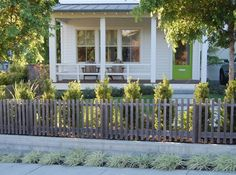 "A house with a modern picket fence (using 2-by-2-inch pieces of clear cedar) designed by Mill Valley architect Kelly Haegglund. ""One of the interesting effects of this design is that it appears almost solid from certain angles then opens up as you look straight on,""  says Haegglund. The natural wood pickets blend seamlessly with the solid cedar backyard fence."