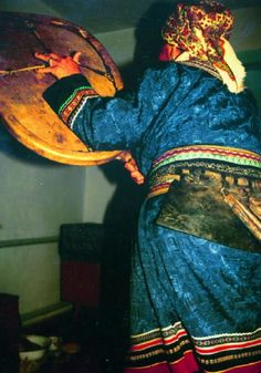 Nanai woman entertaining the spirits by using shamanic belt and a drum (1993)    Photo and description by Mihály Hoppál