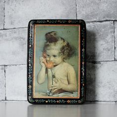 Bonjour,  Lovely tin storage box with a floral decor for 50 or 60. A nice baby girl is holding an orange/red phone.  Pretty in your kitchen for