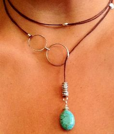 Boho chic necklace with brown leather cord, silver beads and rings and turquoise stone. Lariat style wraps around neck and turquoise stone drops at bottom.