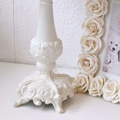 """This ornate lamp base has been painted cream and adorned with a bell-shaped scalloped shade,  made with the finest Dupioni Silk in cream, trimmed with gorgeous large cream Mulberry paper roses.  <BR><BR> • Cream<BR> • Dupioni Silk with Paper Roses<BR> • Handmade to order<BR> • Shade: Bottom: 11.5"""" Bottom Diameter x 9"""" Height<BR> • Lamp Height: 18""""<BR> • Use 40 or 60 watt bulbs<BR> The lamp stands 18"""" tall to the top of the shade. <BR>"""