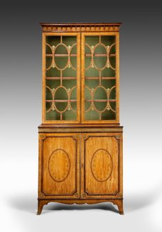 A fine George III simulated satinwood and decorated bookcase on cabinet, in the manner of Mayhew and Ince