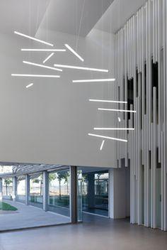 Composición espectacular de lámparas LED lineales #Halo de Vibia en el hall de un edifico público de estilo contemporáneo. Foto de @vibialight