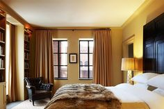 Design firm Janson Goldstein used a David Hicks rug, vintage leather club chair and oversize fur throw to create a luxe, laid-back master bedroom in this New York City penthouse.