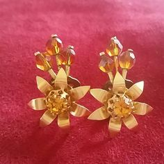 Vintage Austrian goldtone crystal floral earrings Vintage Goldtone floral clip earrings adorned with amber coloured crystals and rhinestone in the center. A little over an inch tall. Vintage Jewelry Earrings