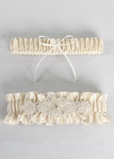 """This champagne garter set is adorned with an elaborate rhinestone and beaded applique. The toss garter is accented with a delicate ivory ribbon. With such an elegant yet classic design the keepsake garter will be an accessory to cherish for years to come.  Features and Facts:   Keepsake garter: 12.5"""" around unstretched, 2"""" width  Toss garter: 12.5"""" around unstretched, 1"""" width  Made of satin with rhinestone and silver bead embellishment"""