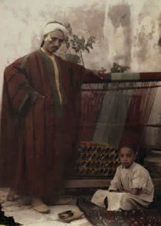 A father and son pose next to a Tunisian weaving machine.