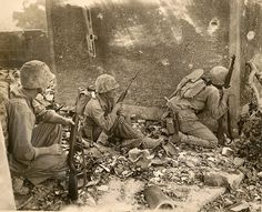 During the fighting in the Okinawan capital, Naha, Marines of the 6th Marine Division take a breather behind a standing wall.