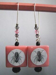 Estos pendientes tienen como bases un par de abalorios cuadrados de color rosa, y sobre los que coloqué con decoupage unas moscas, con una capa de resina transparente. Puede parecer una mezcla un poco rara, así que para darle unidad coloqué unos abalorios tupis en rosa, y de cristal negro.
