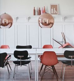 white walls + table + rose gold lighting + pink + black dining chair eclectic mix + wood floor